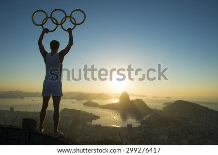 RIO DE JANEIRO, BRAZIL - MARCH 05, 2015: Illustrative editorial of man standing in silhouette holding Olympic rings above city skyline view of Sugarloaf Mountain and Guanabara Bay at sunrise. - stock photo