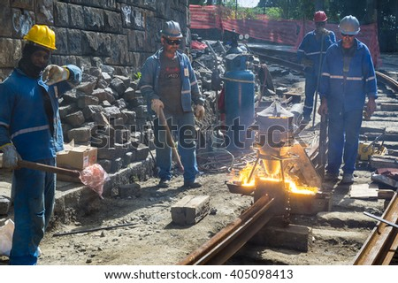 RIO DE JANEIRO - MARCH 24, 2016: Railway construction workers heat metal for trackwork the new bonde in Santa Teresa, where service is being restored after a 2011 accident. - stock photo