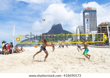 RIO DE JANEIRO - MARCH 17, 2016: Young Brazilian men play a game of futevôlei (footvolley), a sport that combines football/soccer and volleyball, on the beach in Leblon.  - stock photo