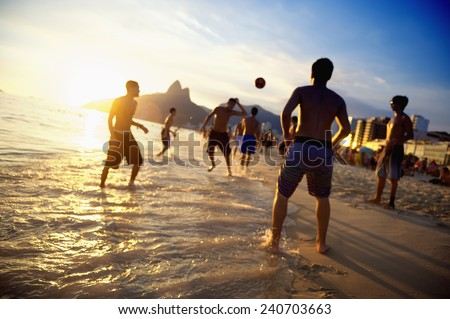 Rio sunset silhouettes of carioca Brazilians playing sunset altinho beach football soccer in sunset waves on the shore of Ipanema Beach Rio de Janeiro - stock photo