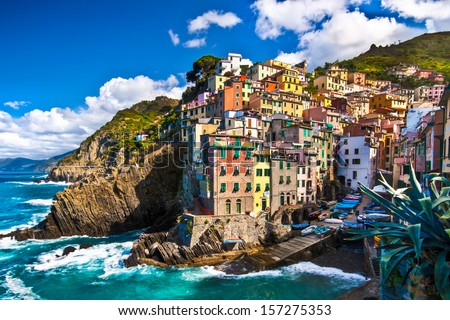 Riomaggiore fisherman village in a dramatic windy weather. Riomaggiore is one of five famous colorful villages of Cinque Terre in Italy, suspended between sea and land on sheer cliffs. - stock photo