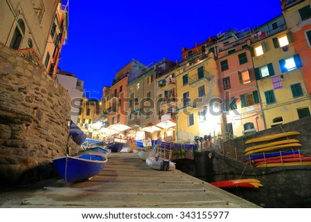 Riomaggiore harbor with old buildings illuminated by the street lights at evening, Cinque Terre, Italy - stock photo