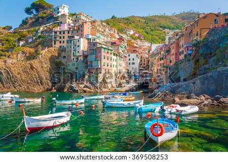 Riomaggiore is the first city of the Cique Terre sequence of hill cities, Liguria, Italy. It has a small dock that provides a good perspective of the shape imposed by the hills around the city. - stock photo