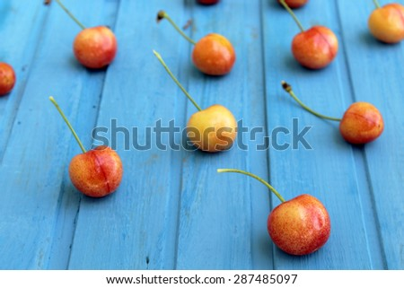 Ripe and fresh cherries on blue background - still life  - stock photo