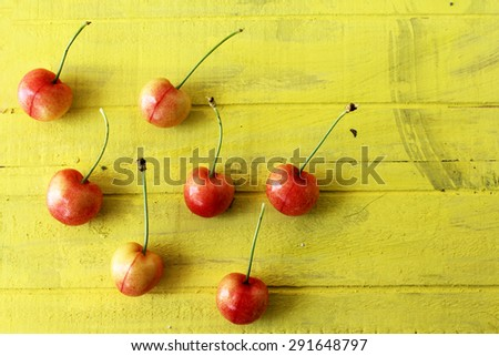Ripe and fresh cherries on yellow background - still life - stock photo