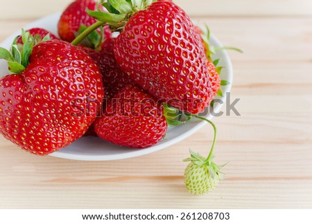 Ripe and unripe berry on a wooden background, closeup, outdoor - stock photo