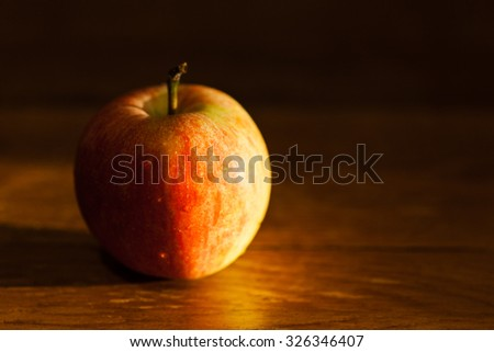 ripe apple fruit on wooden table illuminated by afternoon sunlignt - stock photo