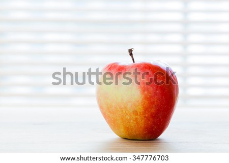 Ripe apple on the table in morning light. Diet breakfast, healthy fresh food. - stock photo