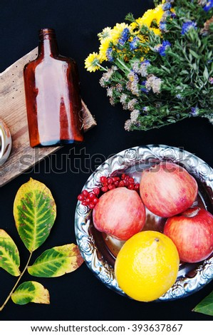 ripe apples in a beautiful plate black background,above view, a bouquet of wildflowers, autumn leaf yellow-green, thick brown bottle, fruit, red apples in a silver plate, lemon yellow, red viburnum - stock photo