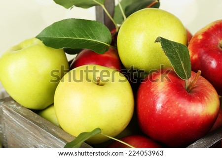 Ripe apples in crate on bright background - stock photo