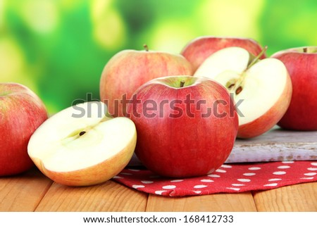 Ripe apples on  wooden table, on bright background - stock photo
