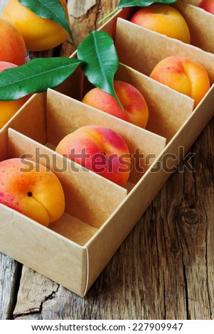 ripe  apricots in a cardboard box on a wooden background.health and diet food - stock photo