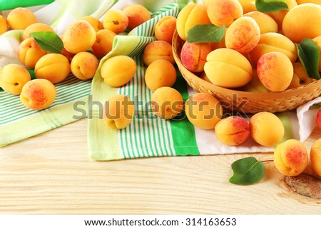 Ripe apricots in wicker bowl on wooden table with napkin, closeup - stock photo