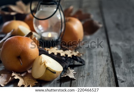 Ripe asian pears, lantern with candle and fall leaves on wooden table. Autumn concept. Selective focus. Copyspace background. - stock photo