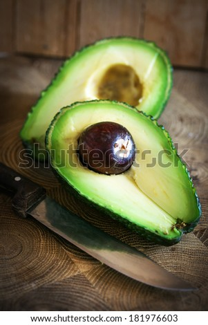 Ripe avocado cut in half on a wooden table/ Fresh avocado on cutting board over wooden background - stock photo