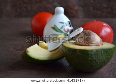 Ripe avocado cut in halves and puree is on a white glass spoon, red tomatoes . Dark background. Stone kitchen counter.  Favorite healthy snack. Healthy dinner inspirations for every day. - stock photo