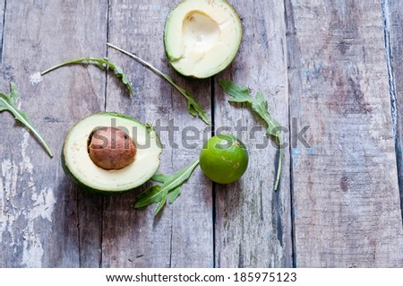 Ripe avocado in half and lime  on a wooden table - stock photo