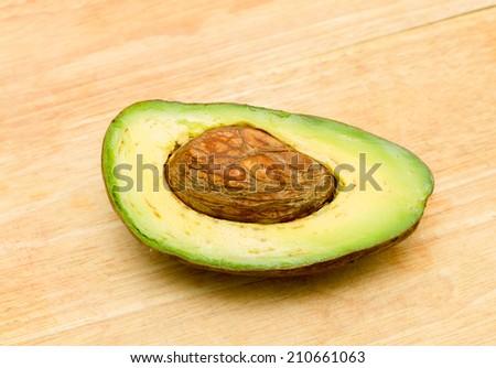 Ripe avocado on wood background - stock photo
