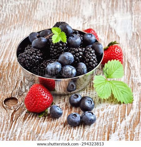 Ripe berries, blueberries, strawberries, blackberries, summer harvest. Fresh vitamins, vintage rustic background, selective focus, toned image, square image - stock photo
