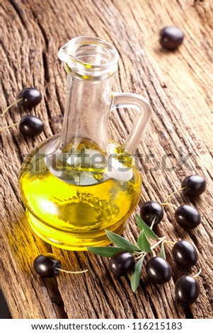 Ripe black olives with leaves on a wooden background. - stock photo
