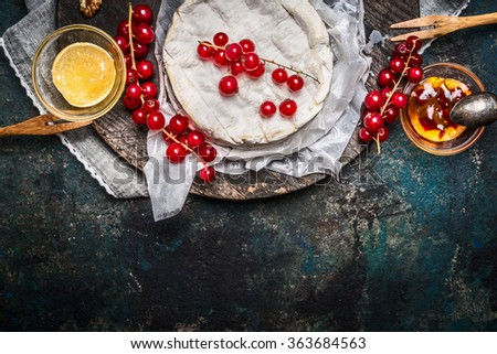 Ripe Camembert cheese plate with red currant berries and sauce on dark rustic background, top view, border - stock photo
