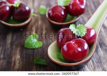 ripe cherries in a ceramic spoon on old wooden background. close-up. health and diet food. selective focus - stock photo