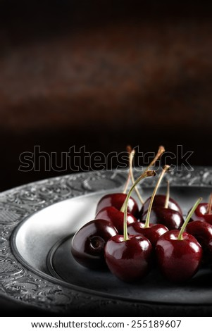 Ripe cherries in a rustic setting shot in natural light. Concept for restaurant dessert menu cover image. Copy space. - stock photo