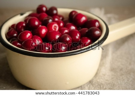 Ripe cherries in vintage colander on wooden rustic background. - stock photo