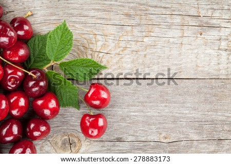 Ripe cherries on wooden table with copy space - stock photo