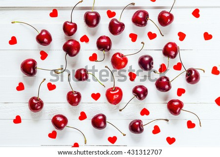 Ripe cherries scattered on a white table with hearts shapes. Cherries with hearts pattern. Top view. - stock photo
