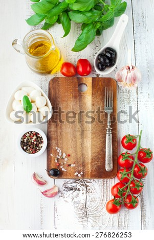 Ripe cherry tomatoes, fresh basil leaves, mozzarella cheese and olive oil for caprese salad on white wooden background, top view - stock photo