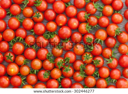 Ripe cherry tomatoes texture on wooden table - stock photo