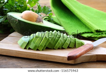 ripe cleaned peeled avocado sliced on the board - stock photo