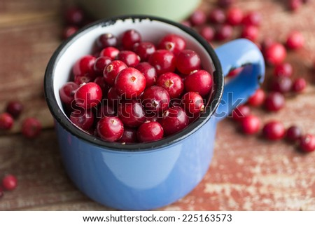 ripe cranberries in cups on a wooden surface - stock photo