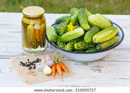 Ripe cucumbers in metal bowl, vegetables and spices for pickling and jar marinated cucumbers on old wooden white table in garden on sunny day - stock photo