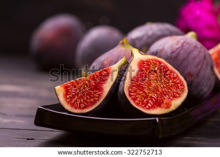 Ripe delicious figs and autumn flowers on black wooden background. Selective focus - stock photo
