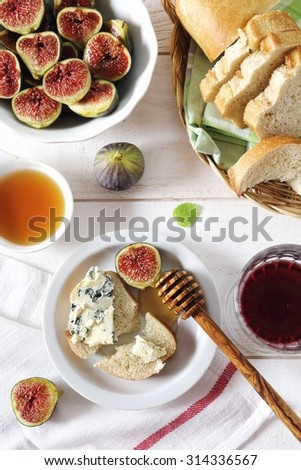 Ripe figs, blue cheese, honey, baguette and glass of red wine - stock photo
