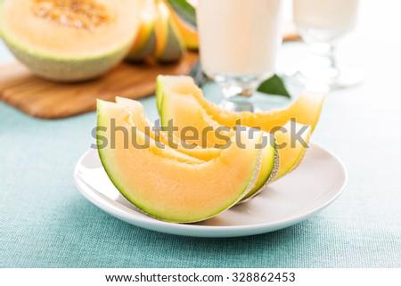 Ripe fresh cantaloupe slices on white plate  - stock photo