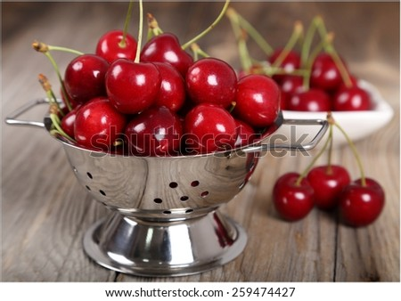 Ripe, fresh cherries in a small colander on a wooden background - stock photo
