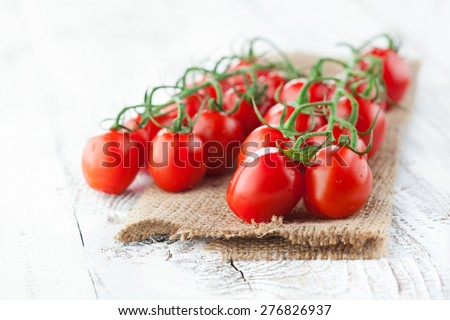 Ripe fresh cherry tomatoes on white wooden background, selective focus - stock photo