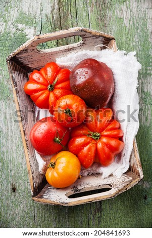 Ripe fresh colorful tomatoes in wooden box on green wooden background - stock photo