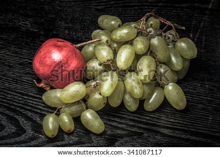 Ripe fresh juicy grape and pomegranate on a black table or board like background. Toned. - stock photo
