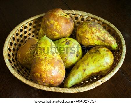 Ripe fresh pears in wicker bowl - stock photo