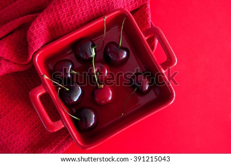 Ripe fresh shiny and juicy cherries in a red square bowl on a table with red kitchen towel. Top view, copy space, different shades of red. - stock photo