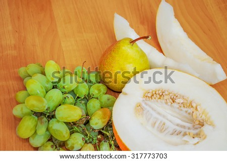 Ripe fruit lies on a table. The melon, a pear, grapes lie on a table.  - stock photo