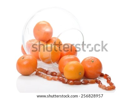 Ripe fruit tangerines in glass vase transparent and from amber necklace still life on white background - stock photo