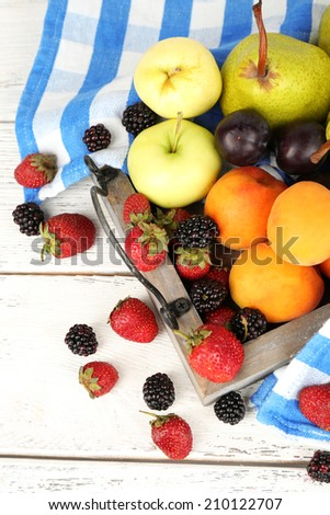 Ripe fruits and berries on wooden tray on table close up - stock photo