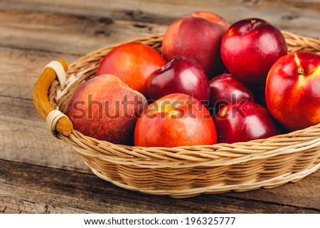 Ripe Fruits in a Woven Willow Basket on Rustic Wooden Table - stock photo