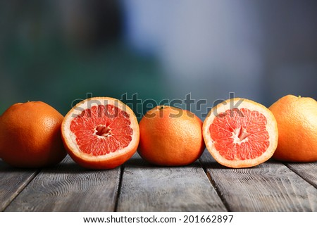 Ripe grapefruits on wooden board, on bright background - stock photo