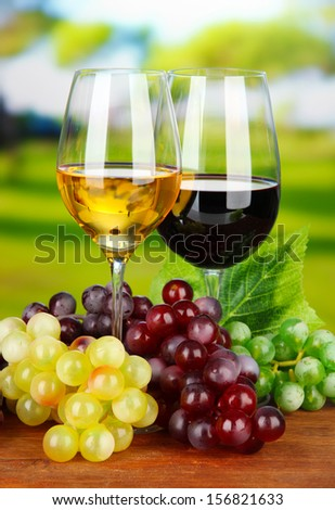 Ripe grapes and glasses of wine, on bright background - stock photo